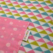 Bata para guardería, con estampado de triángulos y mangas y bolsillo delantero en rosa.