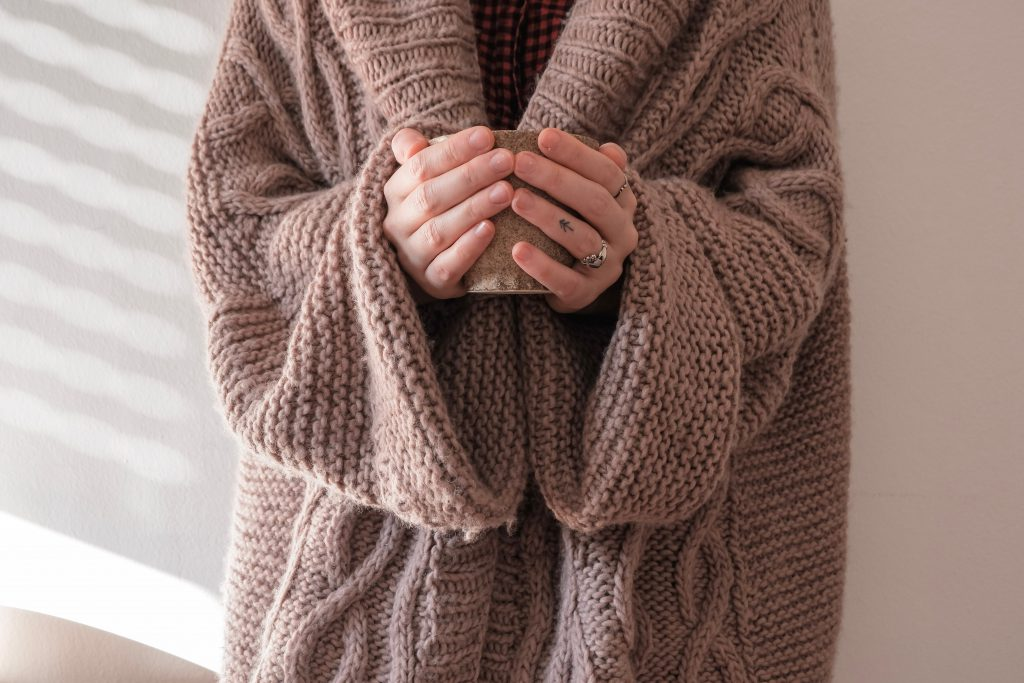 Hygge tips photo of a woman wearing a sweater and holding a cup of coffee