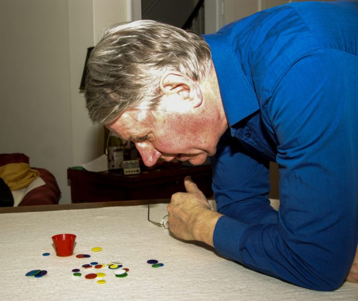 Charles Relle contemplating a shot at the first London Triples tiddlywinks event in Kensington, London.