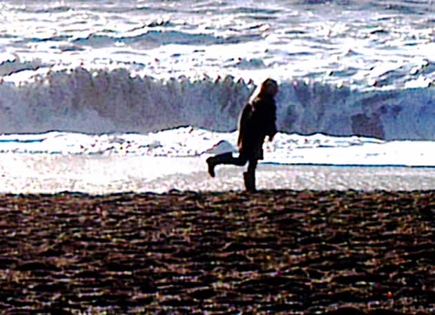 Winter beach - child stands on one leg