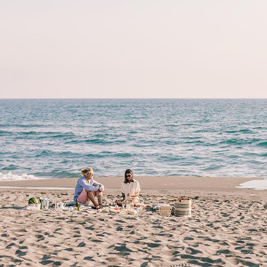 Man and woman enjoying picnic on the beach.