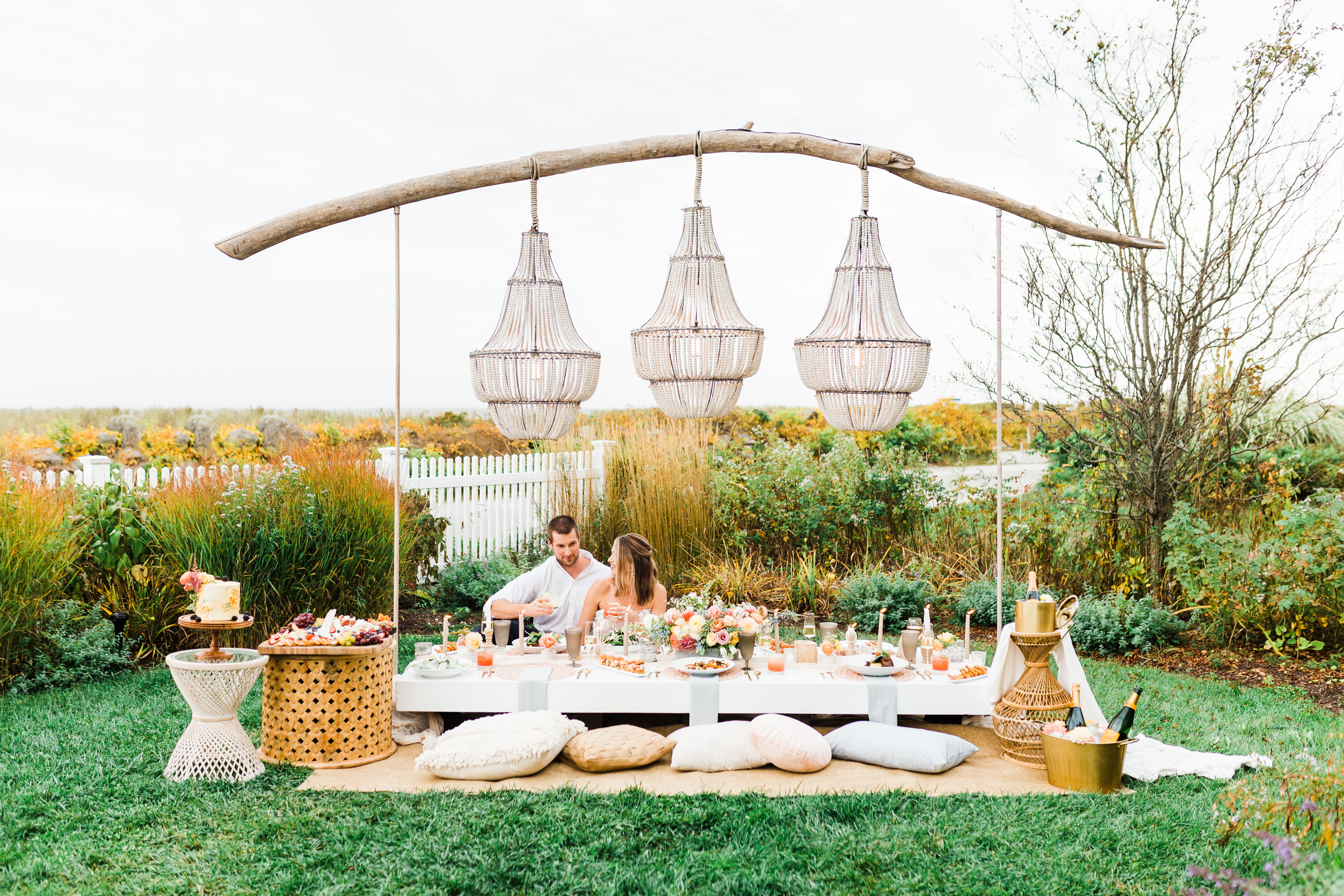 Couple sitting in lawn at picnic table wedding setting