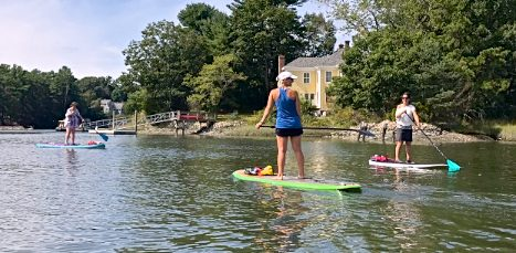 woman standing on stand up Paddleboard teaching yoga in Maine