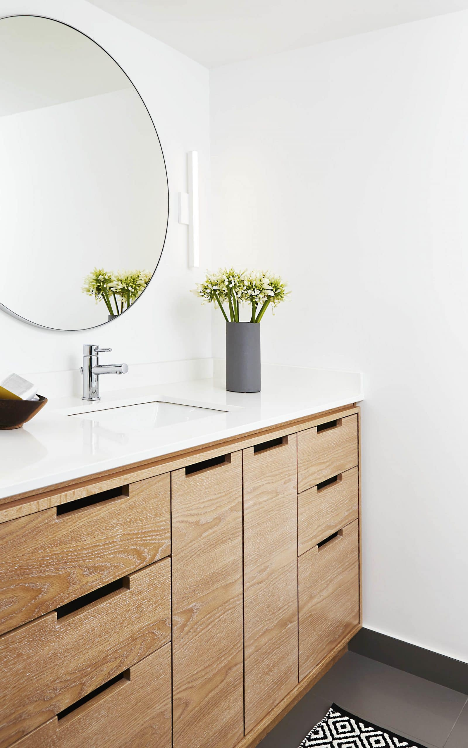 Limed Oak Blonde Wood Bathroom Vanity With Round Mirror White Counter Undermount Sink Chrome Faucet White Sconce And White Walls And Ceiling Toronto Interior Design Group