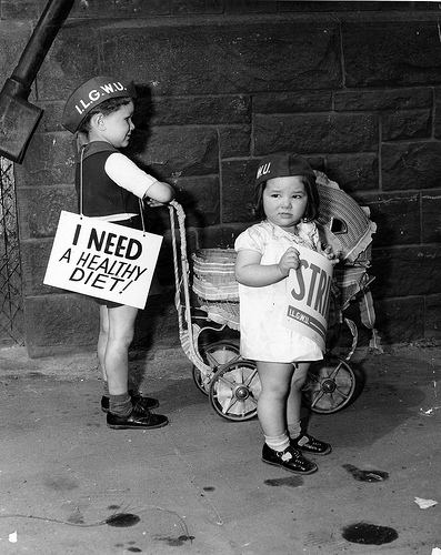 """""""Two young children picket for the ILGWU carrying placards including 'I Need a Healthy Diet!' outside the Kolodney and Myers Employment Office"""" by the Kheel Center at Cornell University, used under CC-BY 2.0."""
