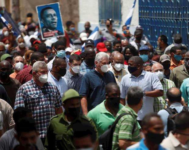 El presidente de Cuba Miguel Díaz-Canel (c) camina acompañado por simpatizantes por una calle del pueblo San Antonio de los Baños (Cuba).