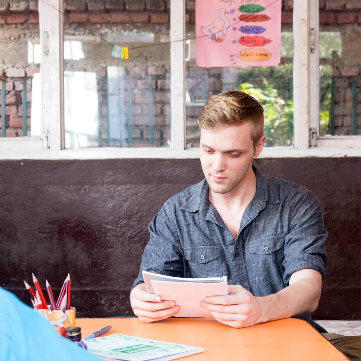 Edward Kobus reviewing paper at sitting desk.