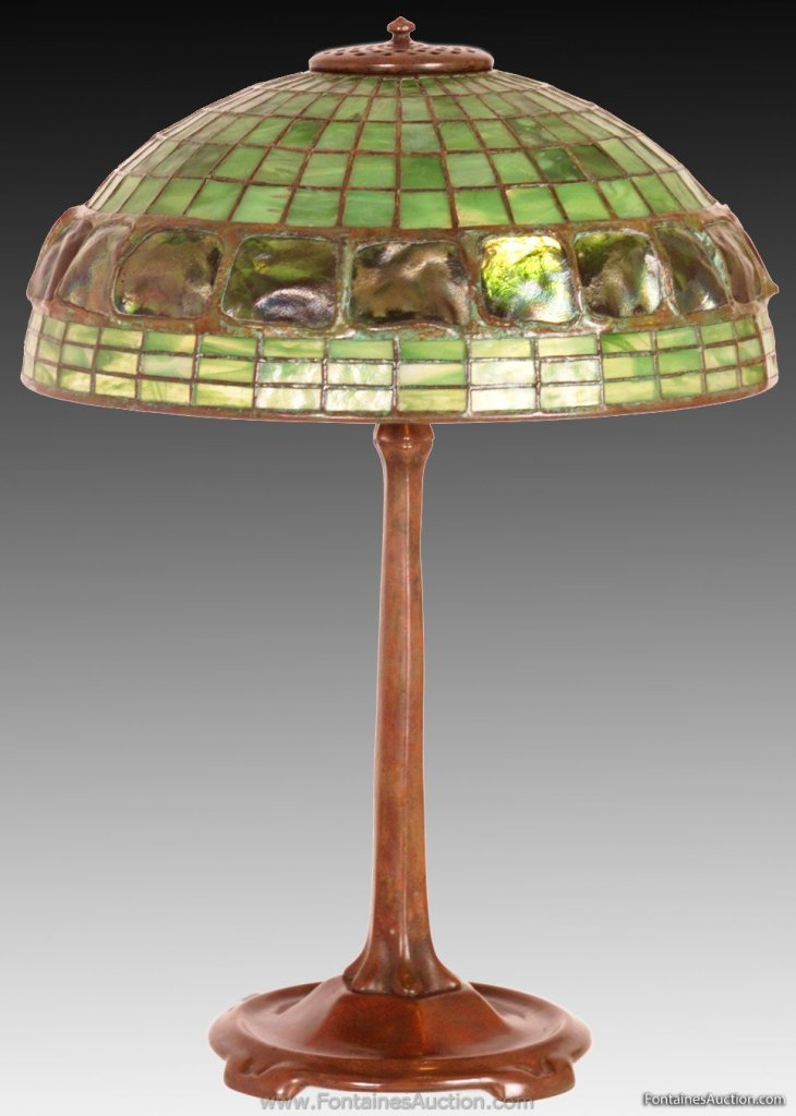 Turtleback Tiffany Shade and Stick base Table Lamp. 21 inches high, 16 inches diameter. Three rows of green mottled glass lead to a wonderful wide band of 19 highly desirable turtleback pieces of glass. Estimate $10,000 - 12,000.
