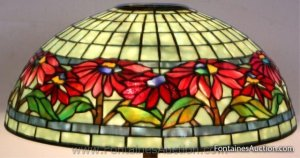 Tiffany Poinsettia Shade. Green mottled background glass, smoke blue mottled borders and red flowers w blue, gold & green centers. Est. $20,000-30,000.