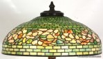 22 in. Tiffany Studios Banded Dogwood Table Lamp. Shade measures 22.5 in. dia., has a geometric staggered brick background in green striated glass