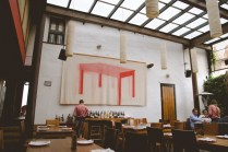 Large open white space with wooden tables, this restaurant is modern meets rustic indoor garden.