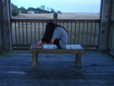 An exhausted young lady sitting on bench at a pier. The last stop on her day trip before heading home.