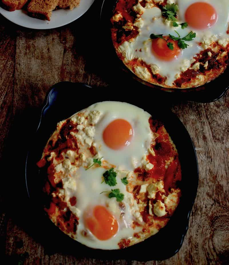 2 Shakshuka dishes with toast on a table