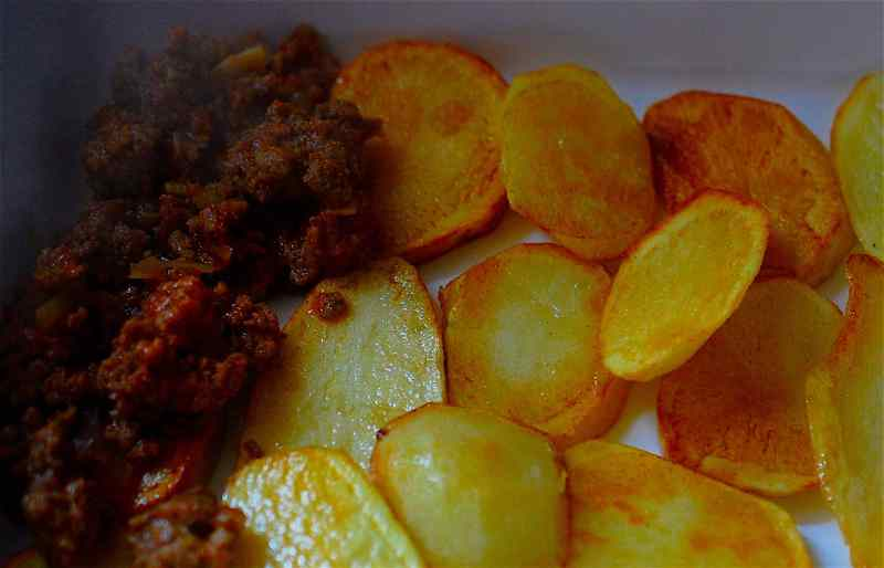 Mince meat layered on some cooked potato slices
