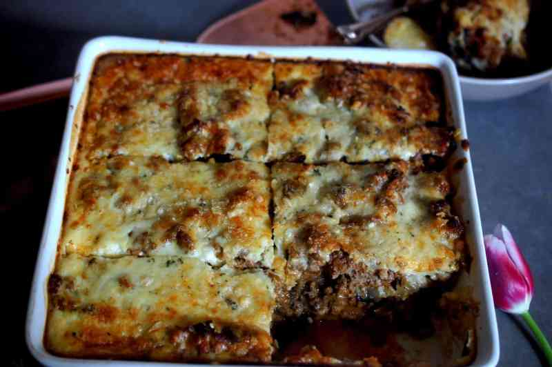 Moussaka in a square baking dish, one slice in bowl