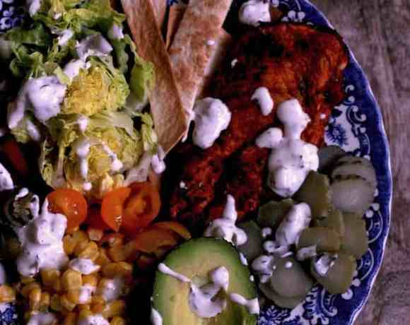 mexican chicken salad on a plate with flatbread strips and sauce