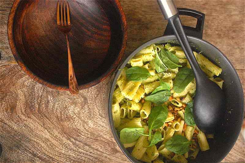 Pasta, spinach, pine nuts in pot with empty bowl to side