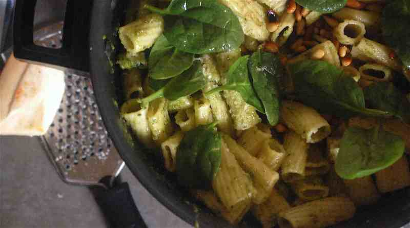 Pasta and spinach in pot with parmesan to side
