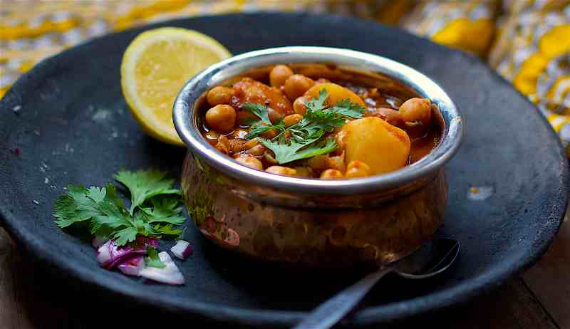 tamarind chana masala in small pot on black plate