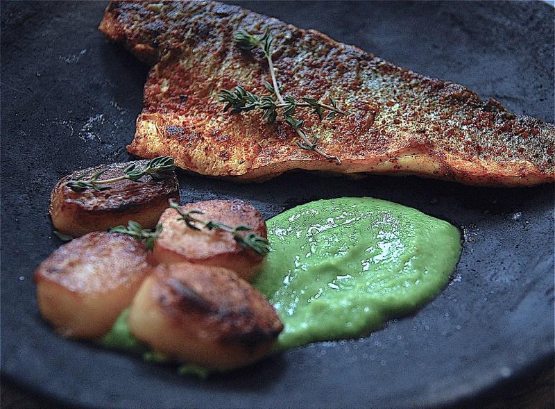 crispy sea bass, fondant potatoes and pea puree in a dark plate