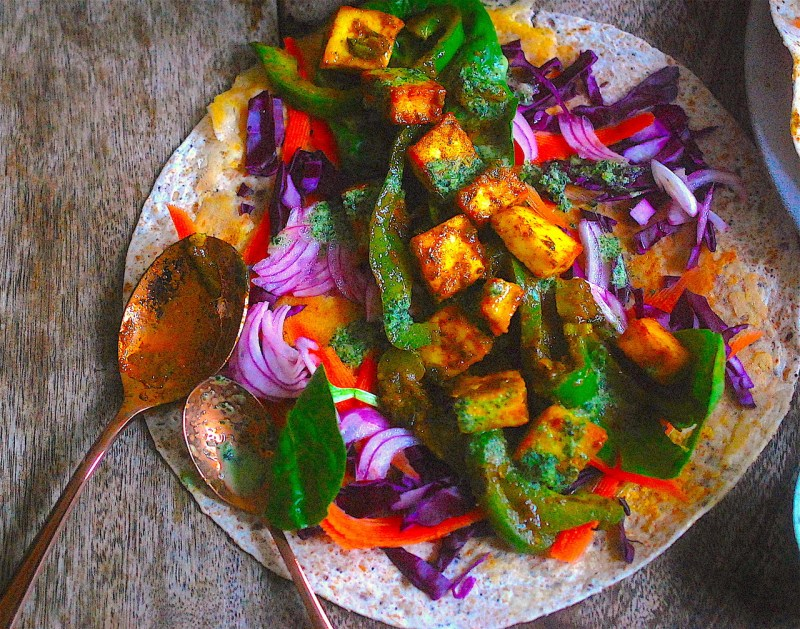 Paneer wraps on a table with mint sauce and red onions