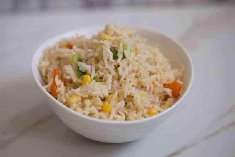 Egg Fried Rice with veg in white bowl on table