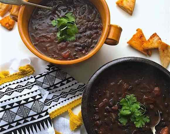 vegan black bean chilli in 2 bowls on white table