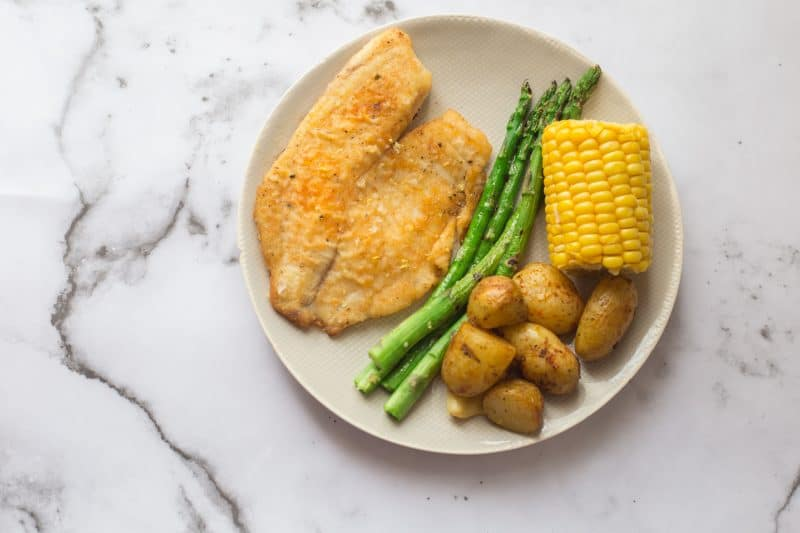 Fish with asparagus, corn on the cob and potatoes on a plate on marble background