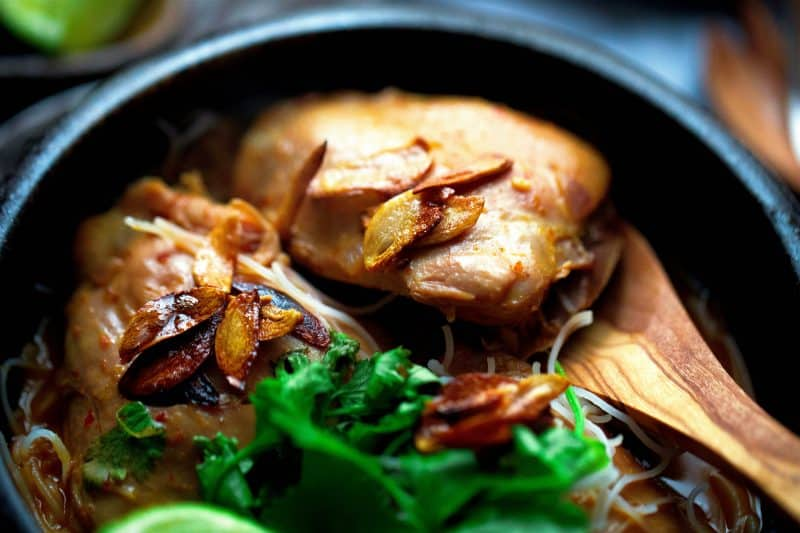 Chicken thighs, fried garlic, rice noodles and kale in bowl with wooden spoon