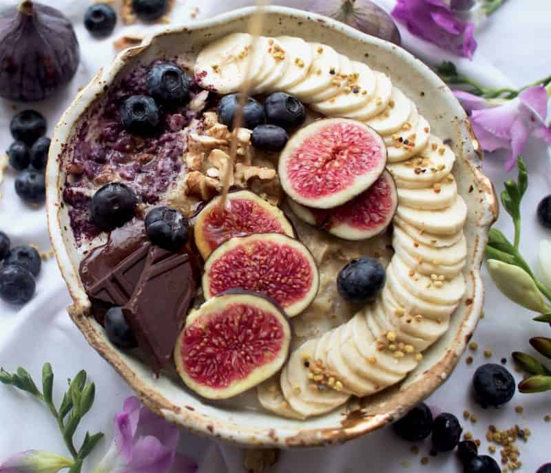 Figs, Blueberry, Banana and Chocolate Porridge in bowl on a white tea towel decorated with figs and flowers