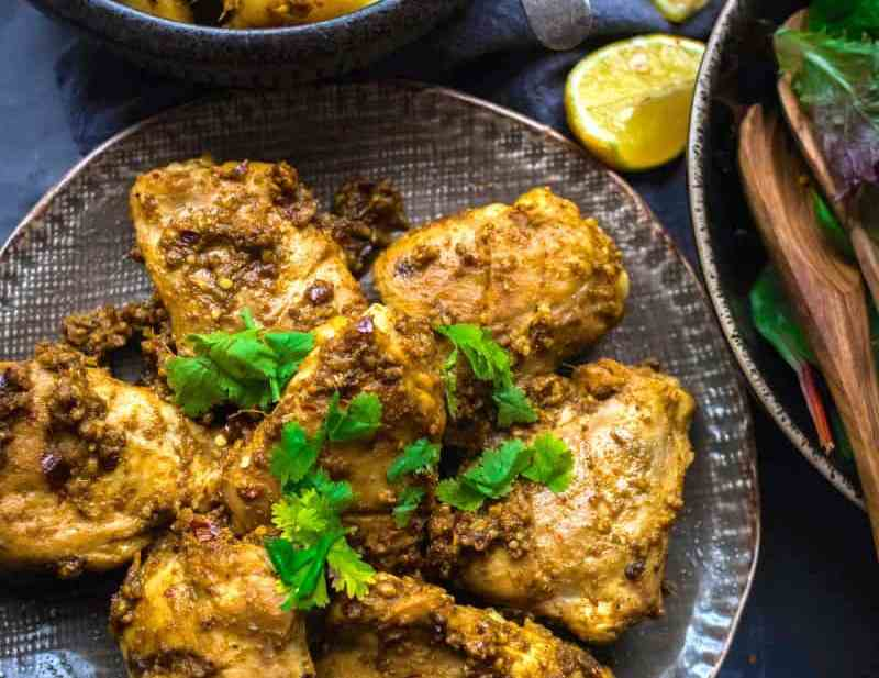 Chicken thighs in a plate with masala sauce and sides