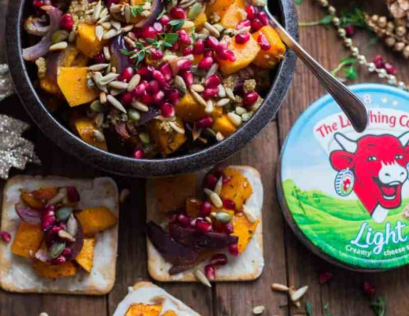 Butternut squash salad in bowl topped with seeds. 3 crackers with laughing cow spread and topped with squash salad on wooden table.