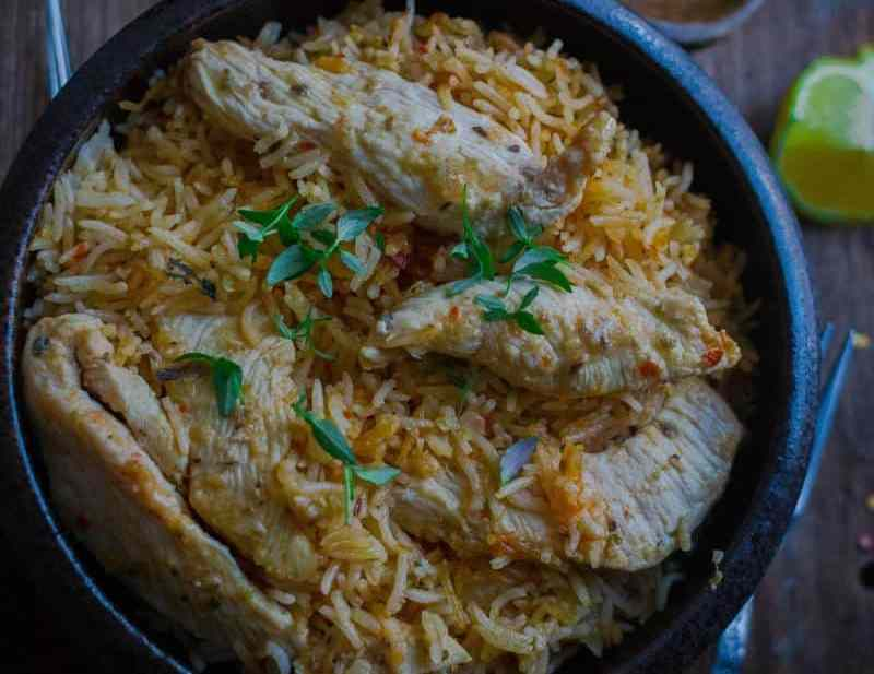 One Pot Peri Peri Chicken and Rice in bowl with lemons dotted around back