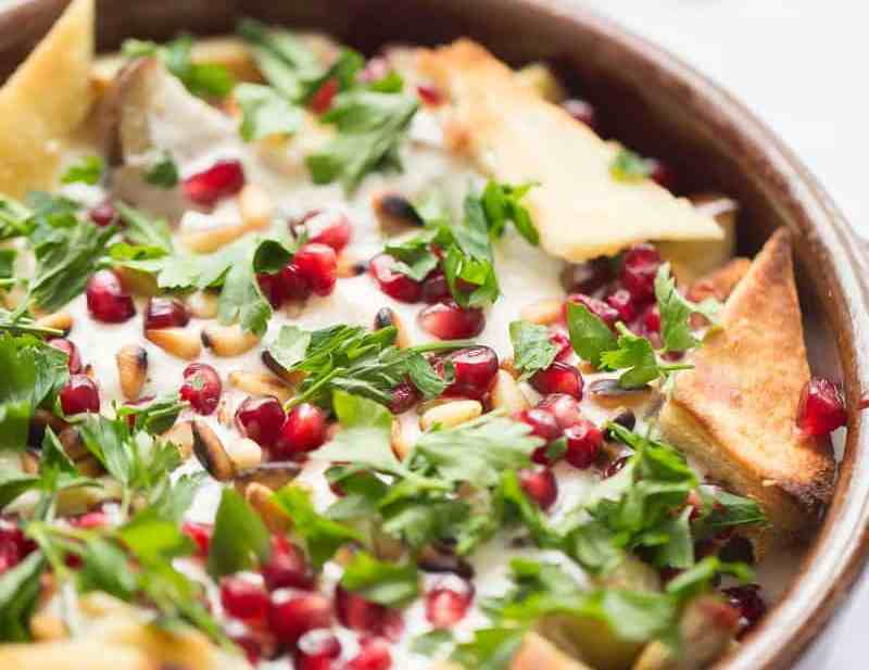 Aubergine Fetteh in bowl topped with pomegranate and toasted pitta