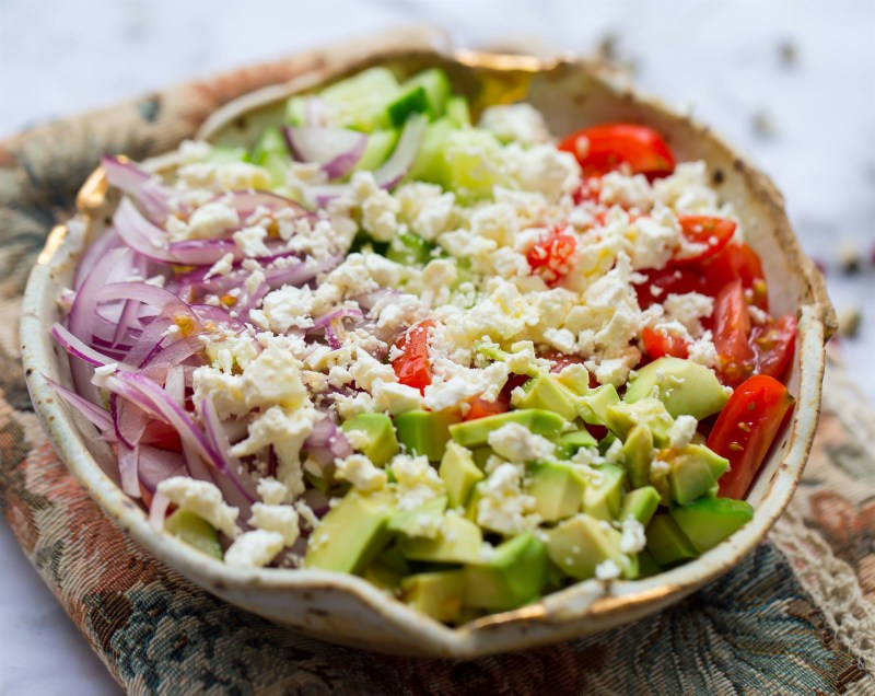 Feta and Avocado Salad with red onions, cucumber and tomatoes in a bowl