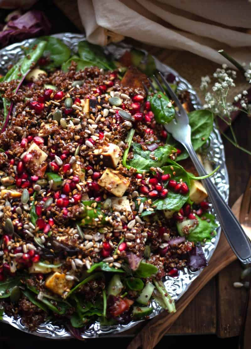 Quinoa on a bed of salad with paneer with seed toppings and pomegranate on silver plate on a wooden board.