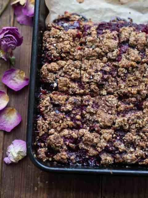 Cherry and Raspberry Crumble Breakfast Bars in baking tray with flowers next to tray