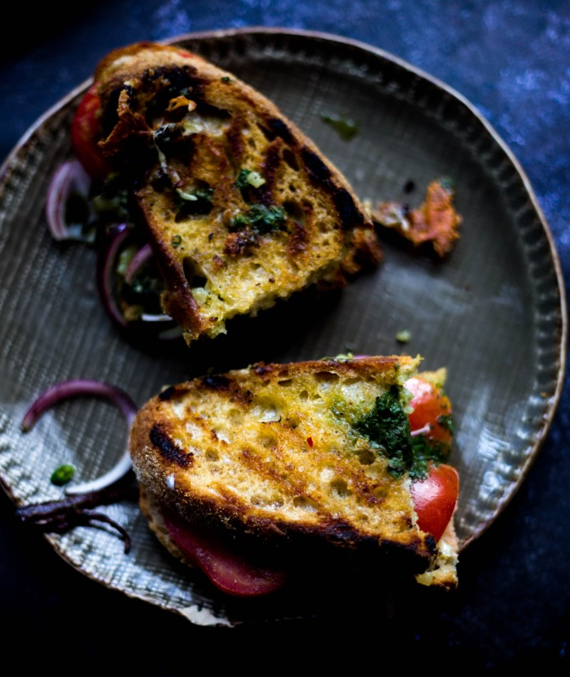 2 Mumbai Sandwich on Crusty White Bread on plate with red onions and crumbs