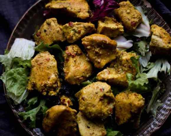 Chicken Tikka pieces on salad in plate