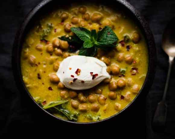 Chickpea stew with dollop of yoghurt and mint leaf in a bowl on a dark background