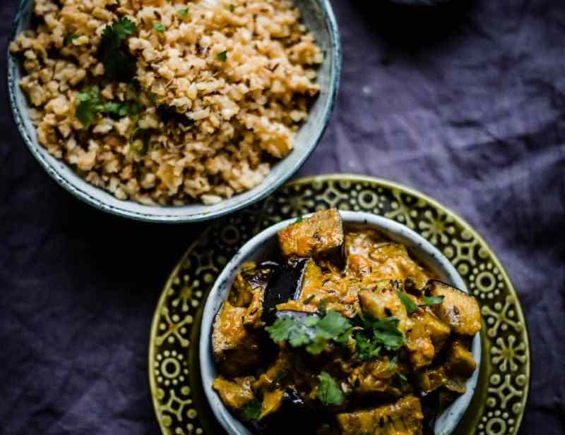 Cumin Cauliflower Rice in a bowl and Creamy Aubergine in another bowl on a grey background