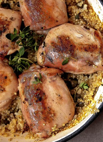 Quinoa with lemon chicken thighs in a pot close up shot.