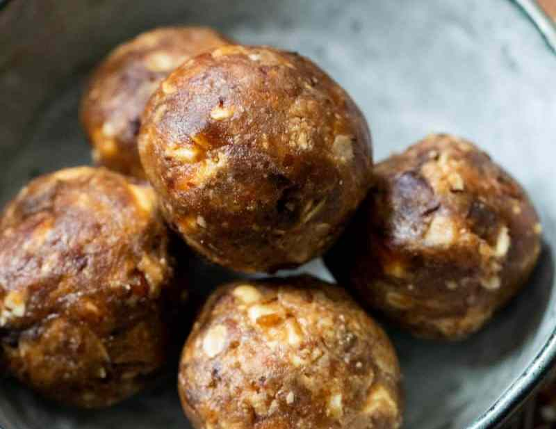 Date and Peanut Butter Balls in a small blue bowl on a patterned wooded circular board