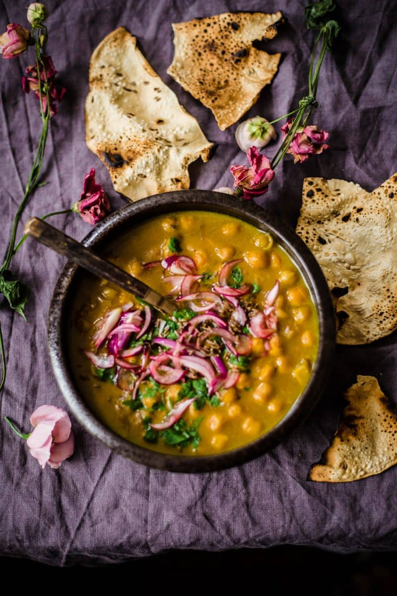 Indian Chickpea, Coconut and Lemon Stew in bowl with popodums scattered around