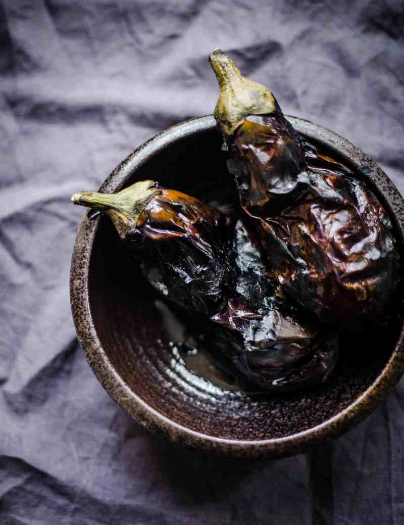 2 charred Aubergines in a black bowl on a grey background