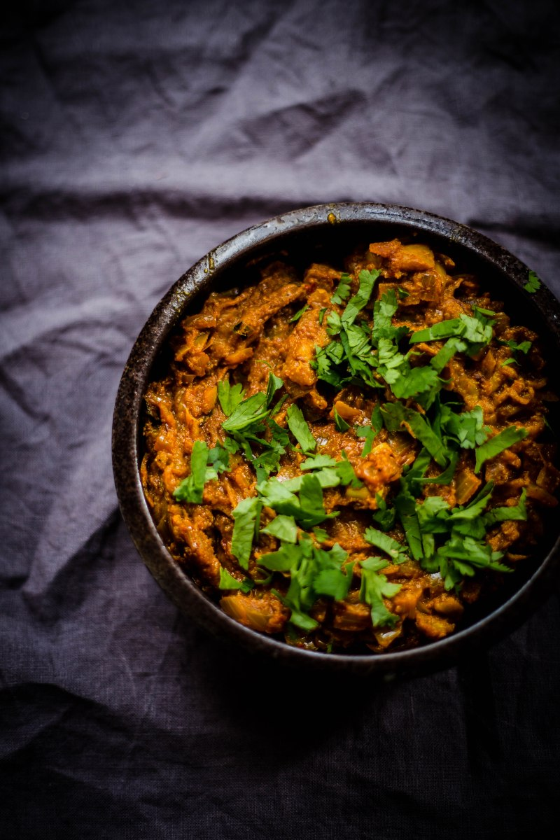 Baingan Barta in a black dish with coriander scattered over on a grey background