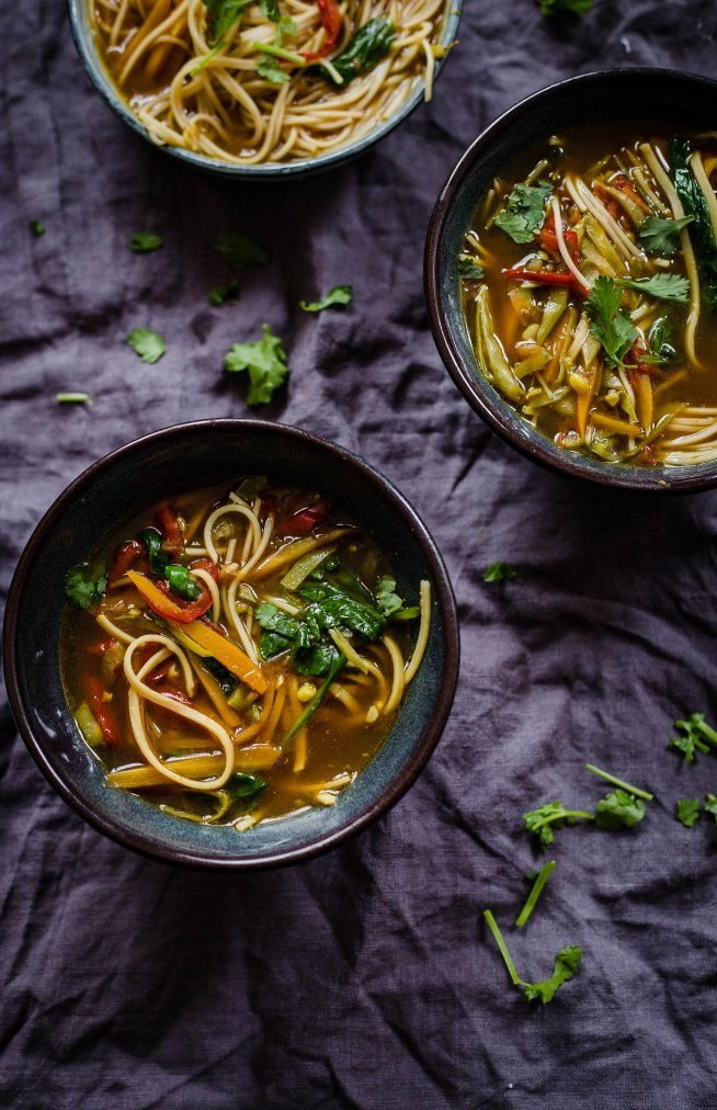 3 bowls of veg noodle soup on a grey creased towel with coriander scattered around the bowl and in the soup