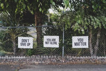 3 signs for self love on a fence