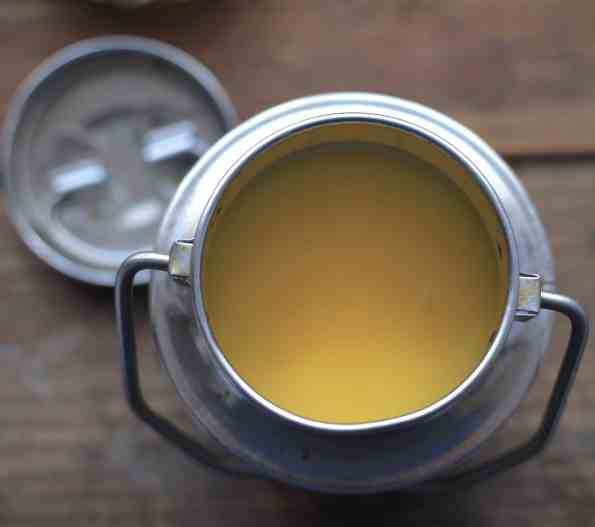 Solid Ghee in indian metal pot on wooden table
