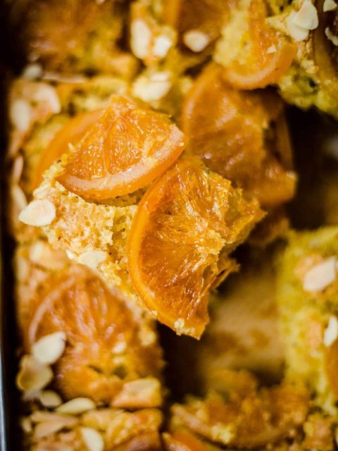 Orange cake sliced with almonds and crystallised oranges on top